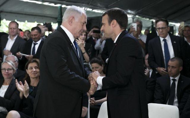 Le président français Emmanuel Macron (d) serre la main du Premier ministre Benjamin Netanyahu lors d'une cérémonie commémorant le 75e anniversaire de la rafle du Vel d'Hiv à Paris le 16 juillet 2017. (Crédit : AFP / Pool / Kamil Zihnioglu)