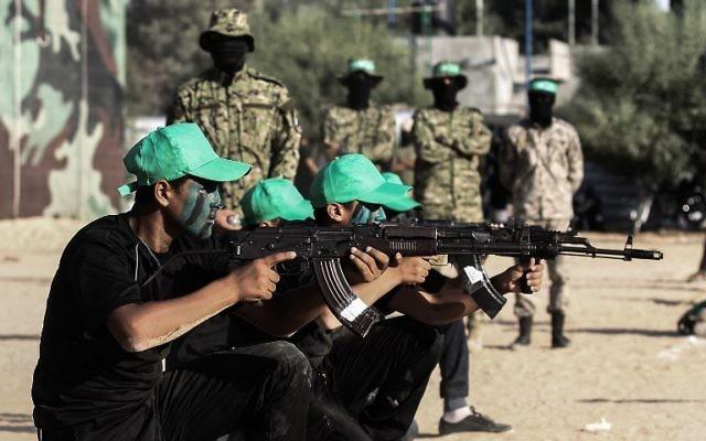 De jeunes Palestiniens participent à une cérémonie de remise de diplômes militaires dans un camp d'été du Hamas à  Khan Yunis, dans le sud de la bande de Gaza, le 18 août 2017 (Crédit : AFP PHOTO / SAID KHATIB)