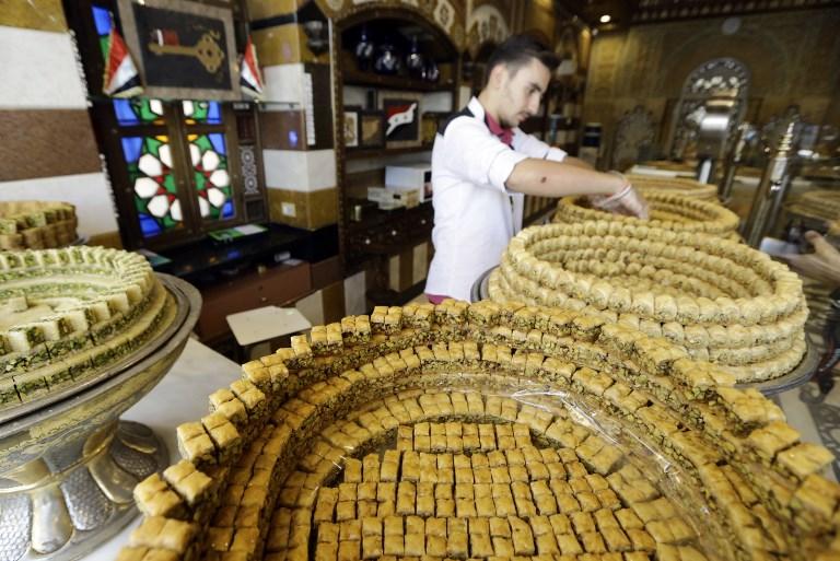 Un employé arrange des pâtisseries syriennes traditionnelles dans un magasin du quartier de Midan à Damas, en Syrie, le 11 septembre 2017 (Crédit : AFP PHOTO / LOUAI BESHARA)