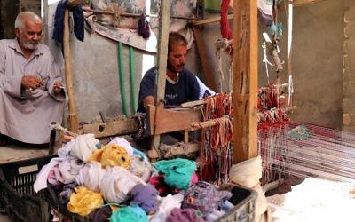 Un homme irakien tisse un tapis dans son atelier de textile dans la ville irakienne de Hilla, au sud de Bagdad, le 12 octobre 2017 (Crédit : AFP PHOTO / SABAH ARAR)