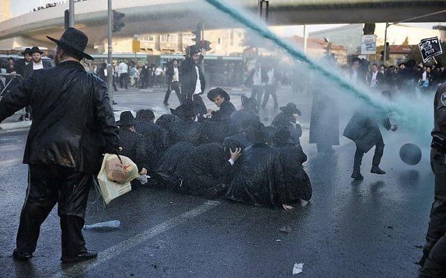 La police pulvérise de l'eau pour tenter de disperser une manifestation de Juifs ultra-orthodoxes contre la conscription de membres de leur communauté, à l'entrée de Jérusalem le 23 octobre 2017. (Crédit :  AFP / Ahmad Gharabli)