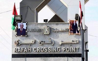 Les portraits du président égyptien Abdel-Fattah el-Sissi et du leader palestinien Mahmoud Abbas dressés au carrefour de Rafah avec l'Egypte, le 1er novembre 2017 (Crédit : SAID KHATIB / AFP)