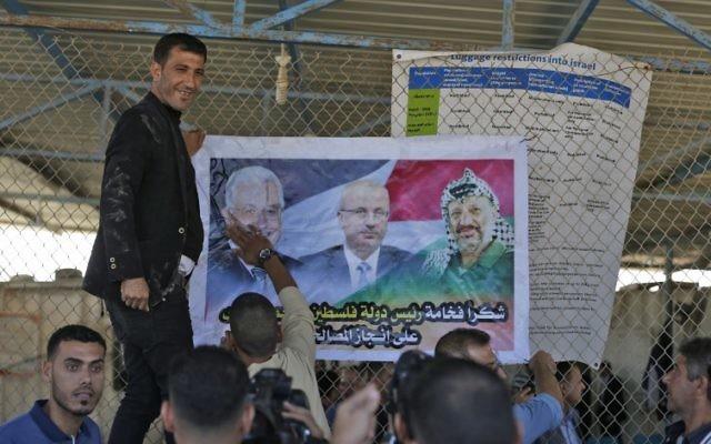 Des Palestiniens mettent un poster à l'effigie du leader palestinien Mahmoud Abbas, à gauche, du Premier ministre  Rami Hamdallah et de feu  Yasser Arafat à l'entrée  nord de la bande de Gaza, juste après le poste-frontière d'Erez contrôlé par les Israéliens, le 1er novembre 2017 à  Beit Hanoun. (Crédit : MAHMUD HAMS / AFP)