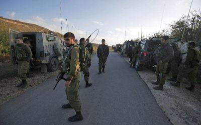 Les soldats israéliens ferment une route à proximité du plateau du Golan pour prévenir l'entrée en Syrie des résidents Druzes après une explosion à la bombe dans le village druze syrien de Hader, le 3 novembre 2017 (Crédit : Jalaa Marey/AFP)