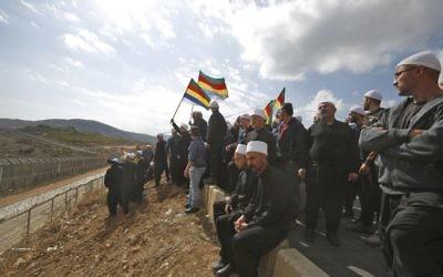 Des hommes druzes dans le Golan israélien se rassemblent à proximité de la frontière syrienne, brandissant leur drapeau communautaire, après avoir entendu parler d'un attentat suicide à la bombe dans le village druze syrien de Hader, le 3 novembre 2017 (Crédit :  Jalaa Marey/AFP)