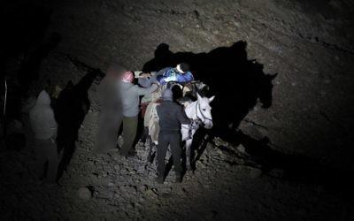 Un Syrien blessé transporté sur un âne à l'approche d'un point de rencontre avec des soldats israéliens sur le mont Hermon sur le plateau du Golan à la frontière entre Israël et la Syrie, avant d'être transféré vers un hôpital israélien pour traitement médical, le 26 octobre 2017 (Crédit : AFP / MENAHEM KAHANA)