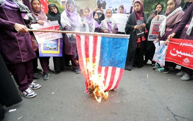 """Des Iraniens brûlent un drapeau américain le 4 novembre 2017 à Téhéran aux cris de """"Mort à l'Amérique"""" (Crédit : AFP/ATTA KENARE)"""