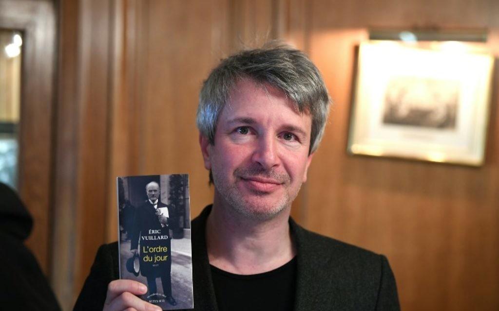 L'écrivaint Eric Vuillard pose avoir son livre après avoir reçu le Prix Goncourt pour L'Ordre du Jour, le 6 novembre2017 au restaurant Drouant à Paris. (Crédit : AFP / Eric FEFERBERG)
