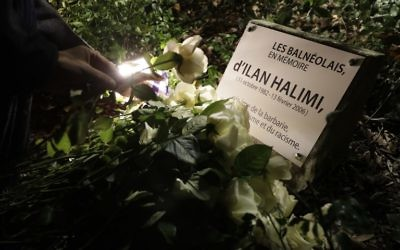 Une personne pose une rose blanche sur la nouvelle plaque  en hommage à Ilan Halimi le 7 novembre 2017 à Bagneux, près de Paris, après une profanation de la plaque commémorative qui a eu lieu le 1er novembre. (Crédit : AFP / Thomas SAMSON)