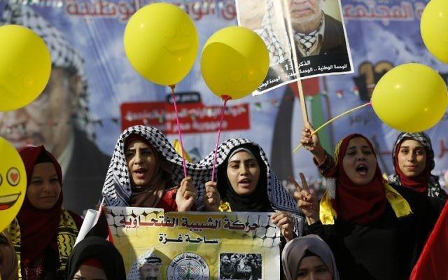 Les palestiniens brandissent des photos de Yasser Arafat à l'occasion du 13ème anniversaire de sa mort, à Gaza-Ville le 9 novembre 2017. (Crédit : AFP/Mohammed ABED)