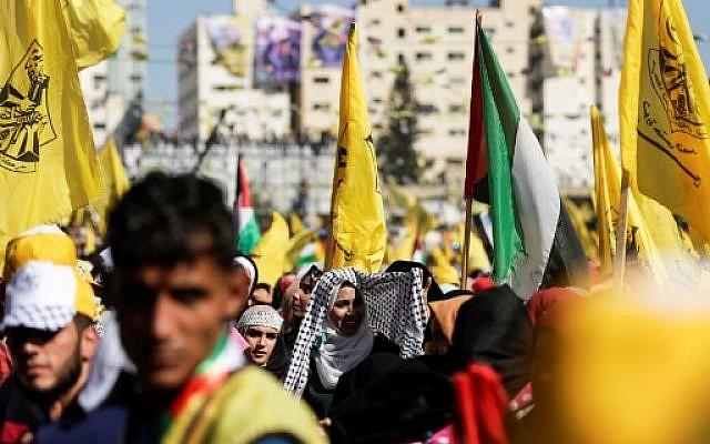 Les partisans du Fatah brandissent le drapeau du parti alors qu'ils participent à un rassemblement dans la ville de Gaza le 11 novembre 2017 (Crédit : AFP / MAHMUD HAMS)