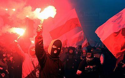 Des manifestants brûlent des torches et brandissent des drapeaux polonais durant une marche annuelle de commémoration de la Journée nationale de l'Indépendance à Varsovie, le 11 novembre 2017 (Crédit : AFP PHOTO / JANEK )