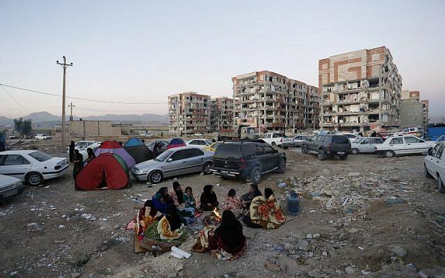 Les habitants se blottissent autour d'un feu dans un espace ouvert suite à un séisme de magnitude 7,3 à Sarpol-e Zahab dans la province iranienne de Kermanshah le 13 novembre 2017. (Crédit : AFP / ISNA / POURIA PAKIZEH)