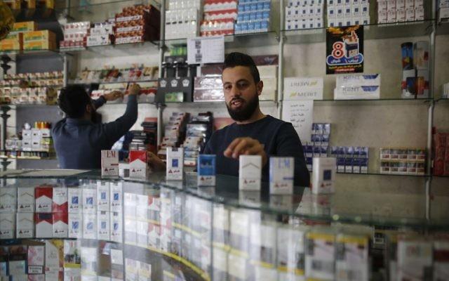 """Des vendeurs palestiniens vendent des cigarettes dans un magasin de la ville de Gaza le 13 novembre 2017. En vertu de l'accord conclu le mois dernier entre le Hamas et l'Autorité palestinienne, l'Autorité palestinienne a immédiatement mis au rancart les taxes et frais """"illégaux"""" - ceux qui ont été imposés par le Hamas durant sa décennie de gouvernement. ainsi que des taxes sur d'autres biens tels que les cigarettes. (Crédit :AFP / MOHAMMED ABED)"""