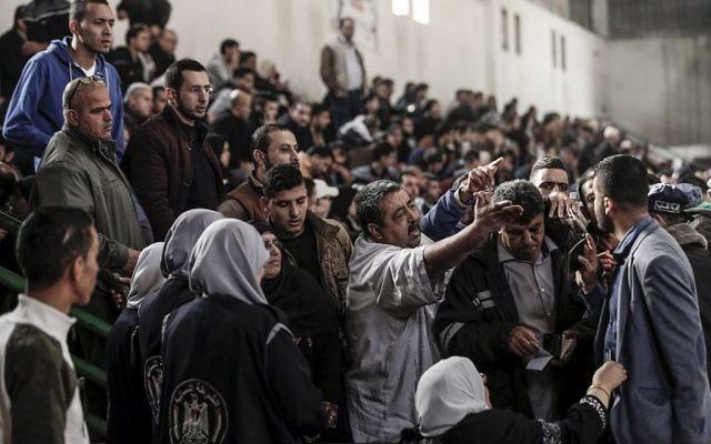 Les Palestiniens discutent avec les responsables du Hamas et les forces de sécurité dans un poste de fortune à Khan Younis, dans le sud de la bande de Gaza, le 18 novembre 2017, attendant de pouvoir prendre un bus pour traverser le poste frontière de Rafah avec l'Egypte. (Crédit : AFP / Mahmud Hams)