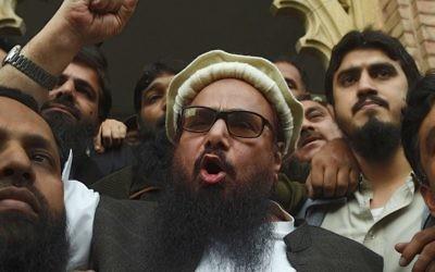 Le chef pakistanais de l'organisation Jamaat-ud-Dawa (JuD) Hafiz Saeed (au centre) s'adresse aux médias après sa libération devant un tribunal de Lahore, le 22 novembre 2017, (Crédit : AFP PHOTO / ARIF ALI)