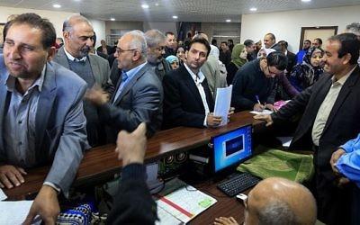 Les fonctionnaires de l'Autorité palestinienne se réunissent pour reprendre leur travail aux quartiers généraux du ministère des Finances à Gaza-Ville, le 29 novembre 2017. (Crédit : AFP PHOTO / MOHAMMED ABED