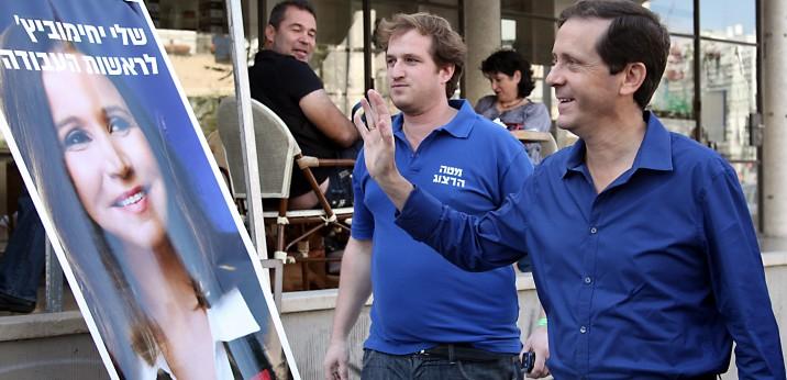 Le député israélien Isaac Herzog se tient devant une affiche électorale pour le chef du parti, Shelly Yachimovich, alors que le parti organise des élections primaires le 21 novembre 2013 (Crédit : Gideon Markowicz / Flash90)