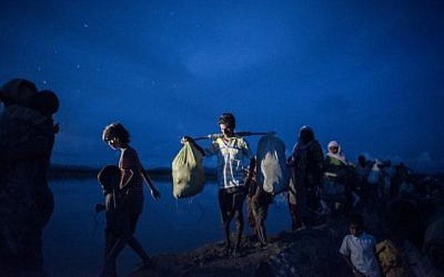 Cette photo prise le 9 octobre 2017 montre des réfugiés Rohingya marchant après avoir traversé la rivière Naf du Myanmar au Bangladesh à Whaikhyang le 9 octobre 2017. (Crédit : AFP/FRED DUFOUR)