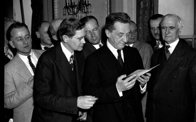 Photo prise en 1938 à Washington, DC : Alexander Kerensky examine le passeport d'un membre de la Croix Rouge américaine, qu'il avait signé en 1917. (Crédit : Domaine public)