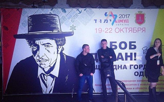 Les participants de la conférence du Limmud FSU, à Odessa, en Ukraine, s'appuient contre une affiche saluant le chanteur Bob Dylan, présenté comme la fierté de la ville, le samedi 21 octobre 2017 (Crédit :  Gavin Rabinowitz/ Times of Israel)