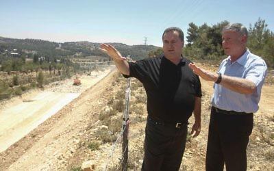 Le ministre des Transports Yisrael Katz, au centre, avec le directeur-général de Netivei Israel Shai Baras, lqui a été ultérieurement arrêté pour népotisme, alors qu'ils inspectaient la construction d'une nouvelle autoroute entre Jérusalem et Tel Aviv, le 12 juin 2013 (Crédit : Flash 90)