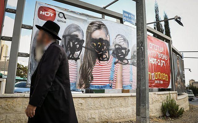 Un ultra-orthodoxe devant une affiche publicitaire vandalisée à Jérusalem, le 2 novembre, 2017. (Crédit : Noam Revkin Fenton/Flash90)