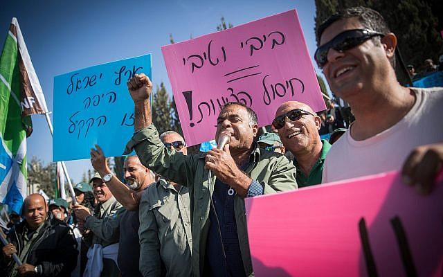 Des travailleurs du Fonds national juif manifestent devant le bureau du Premier ministre à Jérusalem contre une loi exigeant que le JNF/KKL transfère d'importantes sommes de ses revenus au gouvernement, le 12 novembre 2017. (Crédit : Yonatan Sindel / Flash90)