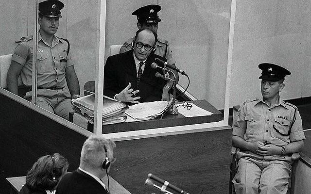 Le criminel de guerre nazi Adolph Eichmann dans une cabine de verre protectrice, entouré par la police israélienne, lors de son procès le 22 juin 1961 à Jérusalem. (Crédit : GPO)