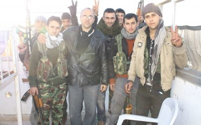 Jonathan Spyer, vêtu d'une veste en cuir noir, rencontre des combattants YPG kurdes dans le nord de la Syrie en 2013. (Crédit : autorisation)