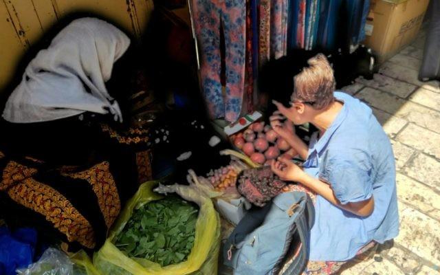 La journaliste Claire Bastier, dans le shouk de la Vieille Ville à côté d'une vendeuse biladie (Crédit: Pierre-Simon Assouline)