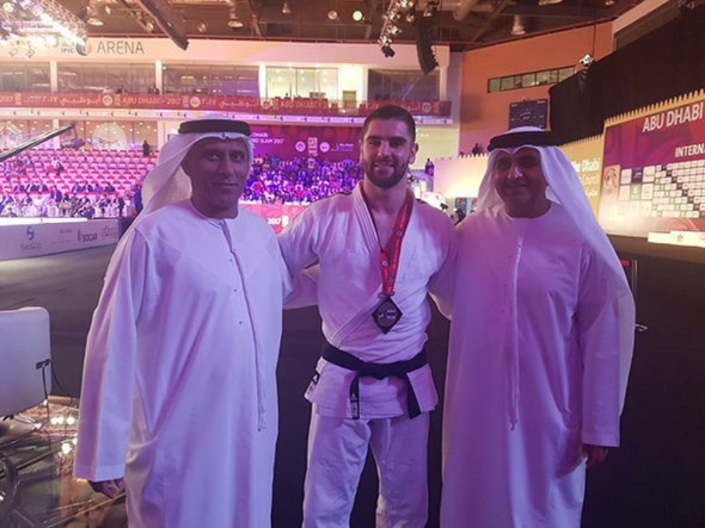 Le judoka israélien Peter Paltchik avec des responsables émiratis lors du Grand Chelem d'Abu Dhabi le 28 octobre 2017 (Crédit : IJF)