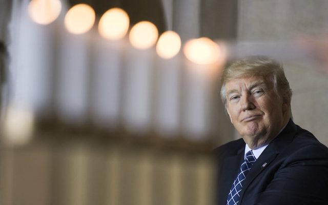 Le président américain Donald Trump regarde l'allumage des bougies de commémoration durant la journée annuelle de commémoration de l'Holocauste lors d'une cérémonie organisée au Capitole, le 25 avril 2017 (Crédit : Tom Williams/CQ Roll Call/Getty Images via JTA)