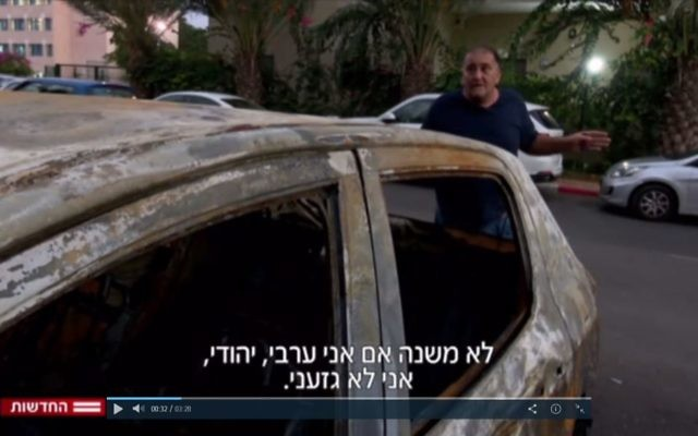 Yoram Israeli à côté de sa voiture incendiée à Netanya le 3 novembre 2017 (Capture d'écran : Deuxième chaîne)