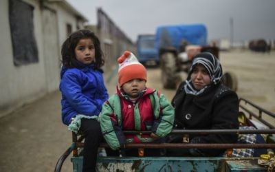 Des enfants réfugiés arrivent à la frontière turque alors que des Syriens fuyant la ville assiégée d'Alep attendent pour passer la frontière, le 6 février 2016 à Bab al-Salama, près de la ville d'Azaz, au nord de la Syrie (Crédit : AFP / Bulent Kilic)