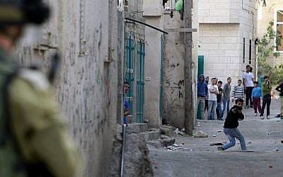 Un émeutier palestinien utilise une fronde pour lancer des pierres contre les forces de sécurité israéliennes lors de la manifestation dans le camp de réfugiés palestiniens de Aida près de Bethléem le 14 avril 2014. (Musa al-Shaer/ AFP)