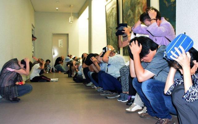 Les riverains protègent leur tête dans un abri, durant un exercice d'évacuation, en cas d'attaque de missiles nord-coréens, à Wajia, dans la préfecture d'Ishikawa,le 30 août 2017, au lendemain du passage d'un missile au dessus du Japon. (Crédit : JIJI PRESS / STR)