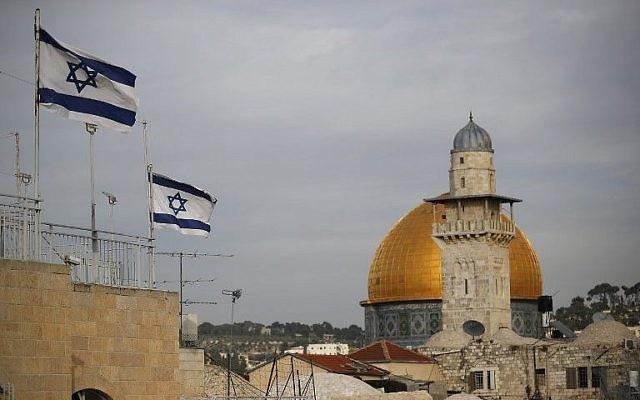 Les drapeaux israéliens flottent au vent alors que le Dôme du Rocher est vu en arrière-plan, dans la Vieille Ville de Jérusalem, le 5 décembre 2017. (Crédit : AFP / Thomas Coex)