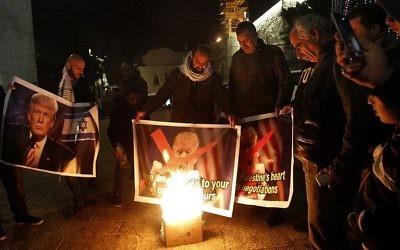 Des manifestants palestiniens brûlent des photos du président Donald Trump sur la place Manger de Bethléem le 5 décembre 2017 (Crédit : AFP Photo/Musa Al Shaer)