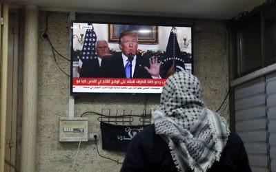 Une photo prise le 6 décembre 2017 montre un Palestinien regardant une allocution prononcée par le président américain Donald Trump, où il annonce la reconnaissance américaine de Jérusalem comme la capitale d'Israël, dans un café à Jérusalem (Crédit : Ahmad GHARABLI / AFP)
