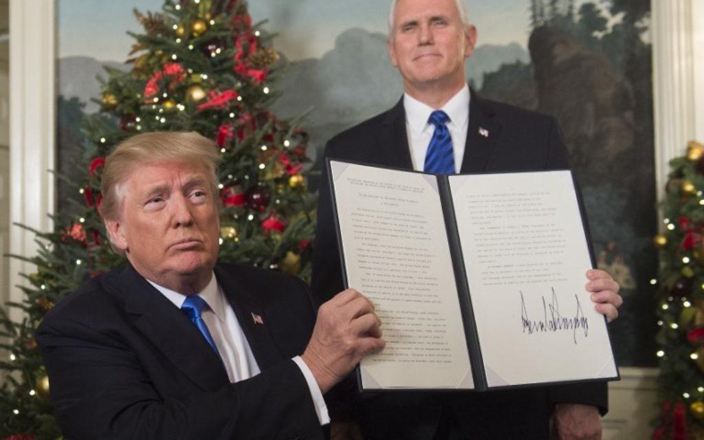 Le président américain Donald Trump tient un mémorandum signé après avoir prononcé son discours concernant Jérusalem depuis la Maison-Blanche, à Washington, le 6 décembre 2017, sous le regard du vice-président américain Mike Pence (Crédit : Saul Loeb / AFP)