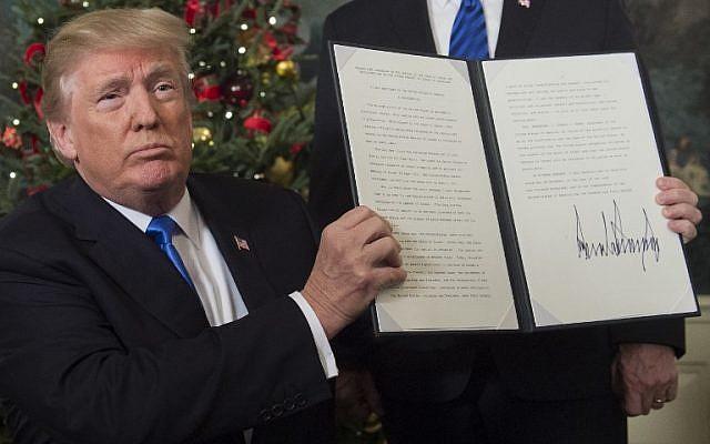 Le président américain  Donald Trump montre le protocole signé reconnaissant Jérusalem en tant que capitale de l'Etat juif dans la salle de réception diplomatique de la Maison Blanche le 6 décembre 2017  (Crédit : AFP PHOTO / SAUL LOEB)