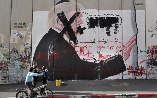 Des enfants palestiniens regardent des graffitis représentant le président américain Donald Trump et des slogans contre le vice-président américain Mike Pence, inscrits sur la barrière de sécurité israélienne à Bethléem en Cisjordanie, le 7 décembre 2017. (Crédit : AFP / THOMAS COEX)
