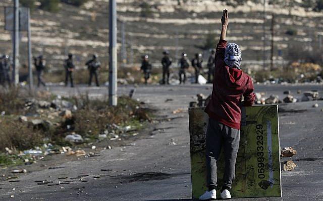 Un manifestant masqué palestinien lors d'affrontements avec les troupes israéliennes près d'un point de contrôle israélien dans la ville de Ramallah en Cisjordanie, le 8 décembre 2017 (Crédit : AFP PHOTO / ABBAS MOMANI)