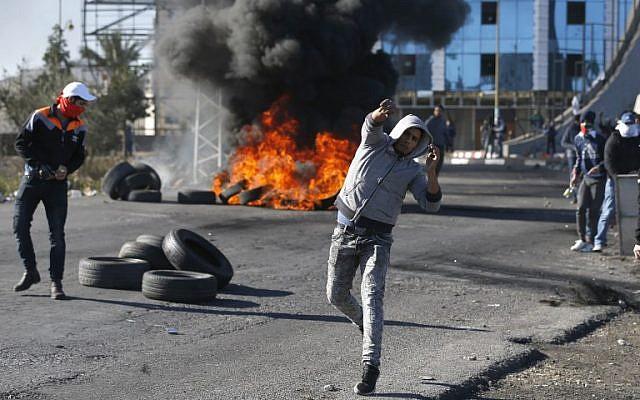 Des émeutiers palestiniens jettent des pierres sur les troupes israéliennes à un point de contrôle israélien près de la ville de Ramallah en Cisjordanie, le 8 décembre 2017 (Crédit : AFP / ABBAS MOMANI)