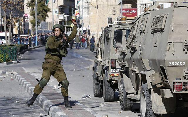 Un soldat israélien lance une grenade sur des émeutiers palestiniens durant des affrontements dans la ville de Hébron, en Cisjordanie, le 8 décembre 2017 (Crédit : Hazem Bader/AFP)