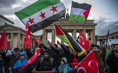 Des manifestants brandissent des drapeaux palestiniens, turques et syriens devant le Brandeburg Gate, près de l'ambassade américaine à Berlin, le 8 décembre 2017. (Crédit : John MACDOUGALL)