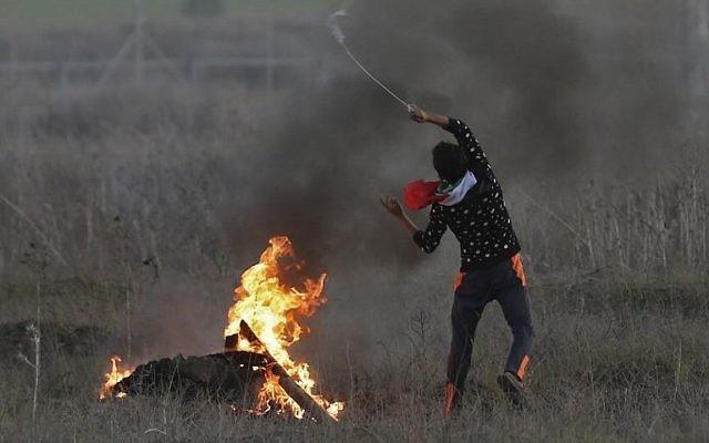 Un émeutier palestinien lance une pierre sur les soldats israéliens pendant des affrontements près de la frontière entre l'Etat juif et Gaza, suite à a reconnaissance par Trump de Jérusalem comme capitale israélienne, le 9 décembre 2017(Crédit :  AFP/Mahmud Hams)