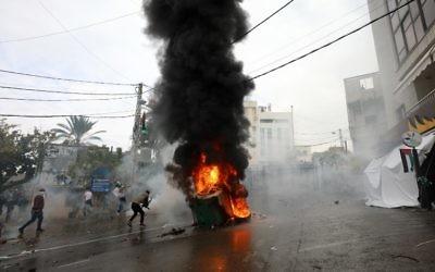 Les forces de sécurité libanaises lancent des gaz lacrymogènes pour disperser les manifestants alors qu'une benne à ordures est en feu lors d'une manifestation devant l'ambassade américaine à Awkar, aux abords de la capitale libanaise Beyrouth, le 10 décembre 2017. (AFP / ANWAR AMRO)