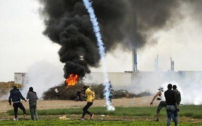 Une photo prise le 10 décembre 2017 montre une cartouche de gaz lacrymogène tombant près des manifestants palestiniens lors d'affrontements avec les forces israéliennes près de la frontière entre Israël et Gaza à l'est de la ville de Khan Yunis, dans le sud de la bande de Gaza (Crédit : PHOTO AFP / MAHMUD HAMS)